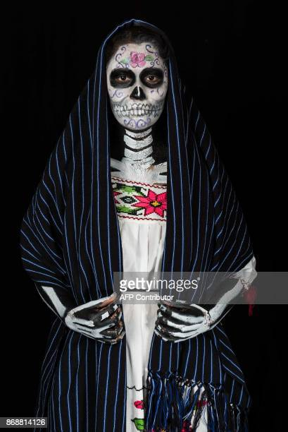 Student Aranza Atienzo Lopez poses for a photograph disguised as Catrina during a Catrina competition at the University of Michoacan in Morelia...