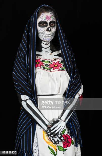 Student Aranza Atienzo Lopez poses for a photograph disguised as Catrina during a Catrinas competition at the University of Michoacan in Morelia...