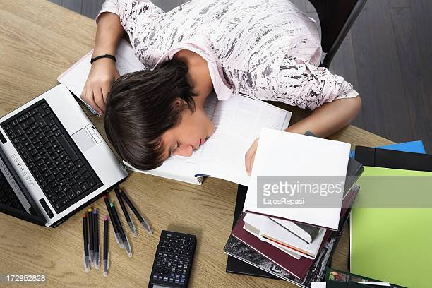 A student asleep on book with books laptop and supplies near