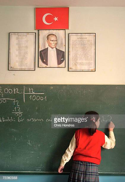 A student at a private school writes on a blackboard under a Turkish flag and a picture of modern Turkey's founder Ataturk January 8 2003 in...