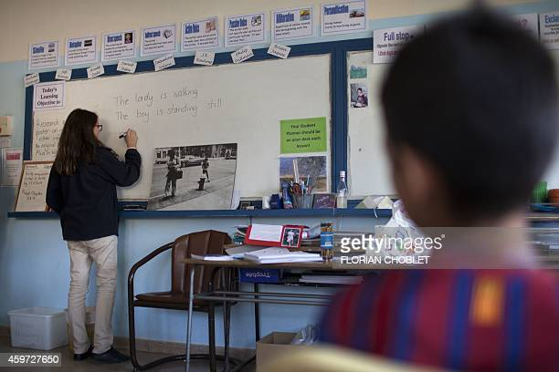 A student at the American Academy in Nicosia who volunteered to teach english to young Syrian refugees gives a lesson on November 11 in the capital...