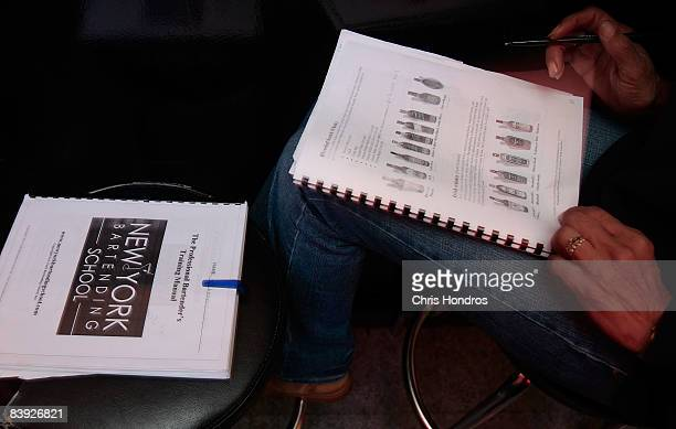 A student at the New York Bartending School looks over her notes and instructional booklets December 5 2008 in New York City Enrollment is up at the...
