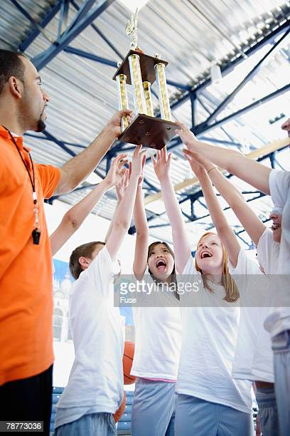 Student Basketball Team Holding Trophy