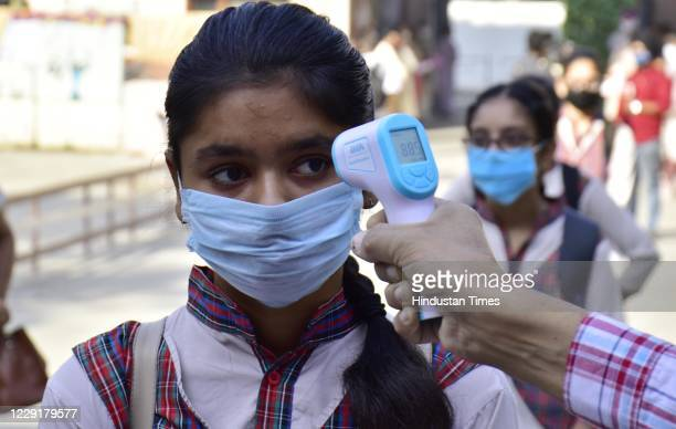Student being thermally screened while entering the school campus after schools reopened partially during the coronavirus outbreak, at Government...