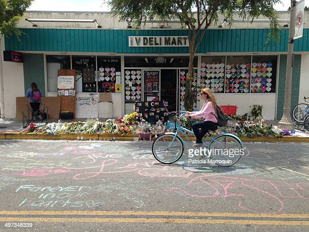 Student bicycles past a makeshift memorial in front of IV Deli Mart in Isla Vista, California. On May 23 Elliot Rodger went on a killing spree and...