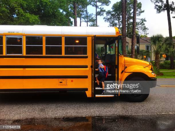 student boarding school bus in city - school bus stock pictures, royalty-free photos & images