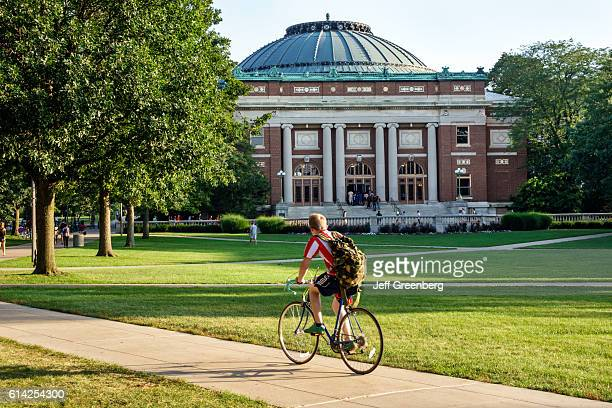 Student boy riding bicycle on campus of the University of Illinois.