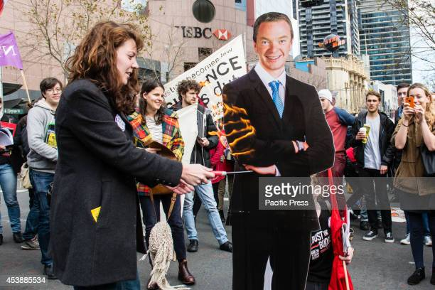 A student burns a cardboard figure of Australia Education Minister Christopher Pyne at a Sydney students protest against Abbott government's budget...