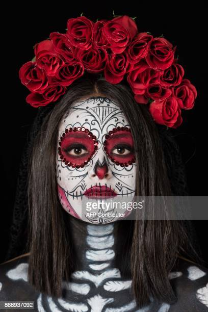 Student Carla Reyes poses for a photograph disguised as Catrina during a Catrinas competition at the University of Michoacan in Morelia Mexico on...
