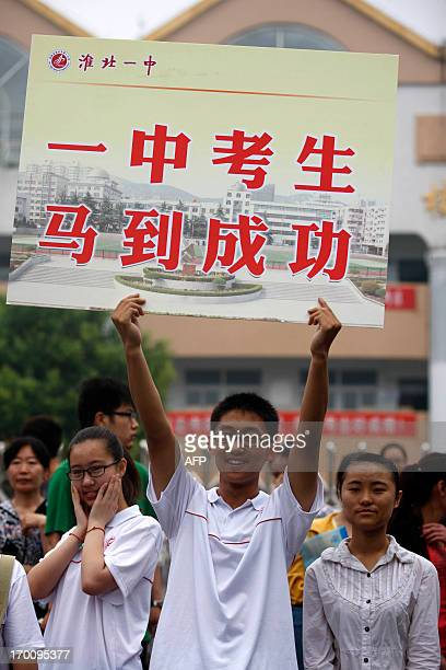 Student carries a banner wishing students good luck for the 2013 university entrance exam at Xiyuan Middle School in Huaibei, north China's Anhui...