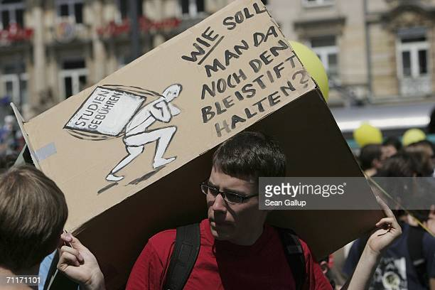 A student carries a box that reads 'Student Fees How Can One Then Even Carry a Pencil' while marching with others against the introduction of student...