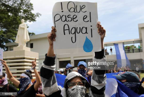 """Student carries a sign reading """"Let the water pass"""" during a protest of students and relatives of political prisoners, in Managua on November 19,..."""