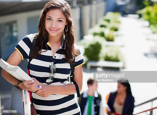 Student carrying book on steps outdoors