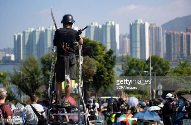 Student carrying bow and arrows during the demonstrations An unprecedented battle took place at the Chinese University Hong Kong as Hong Kong...