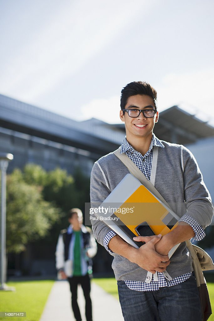 Student carrying folders outdoors : Stock Photo