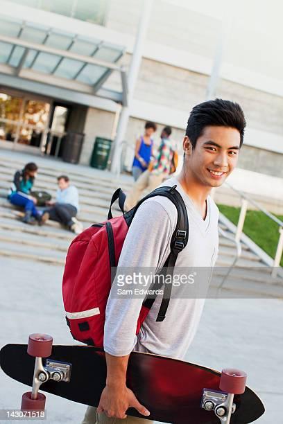 estudante carregando skate ao ar livre - patio de colegio - fotografias e filmes do acervo