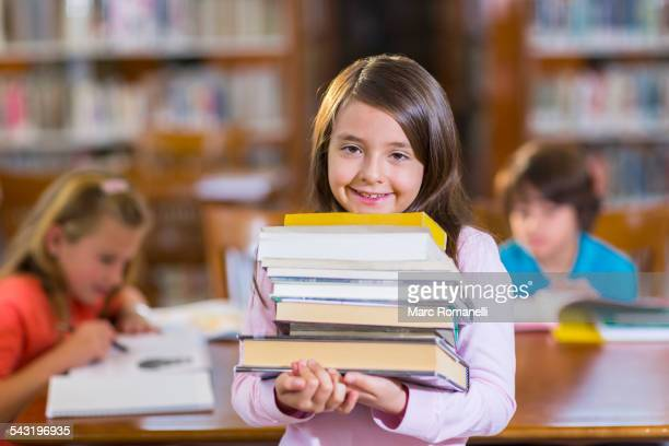 Student carrying stack of books in library
