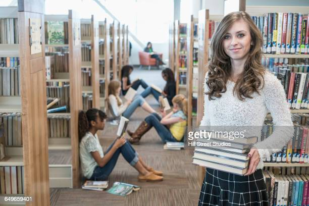 student carrying stack of books in library - girls in plaid skirts stock photos and pictures