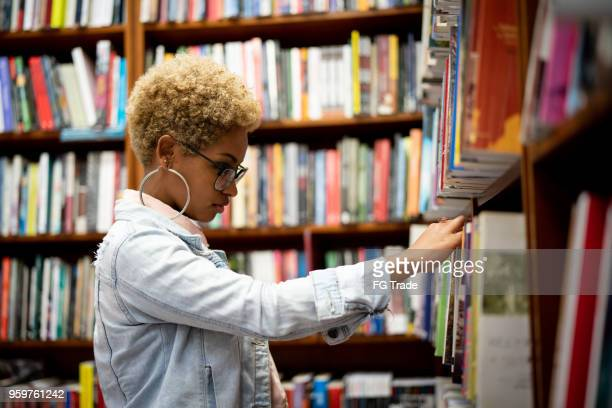 student choosing a book on library - library stock pictures, royalty-free photos & images