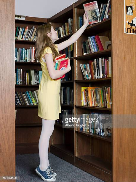 Student choosing book from shelf in library