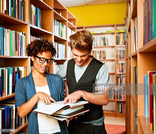 Student choosing books in library