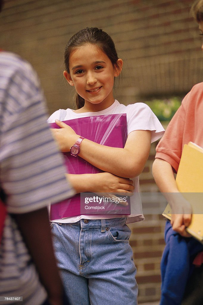 Student clutching her notebook outdoors : Stockfoto