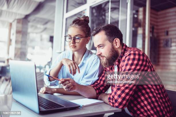 student colleagues drinking coffee and working on laptop - certificate stock pictures, royalty-free photos & images