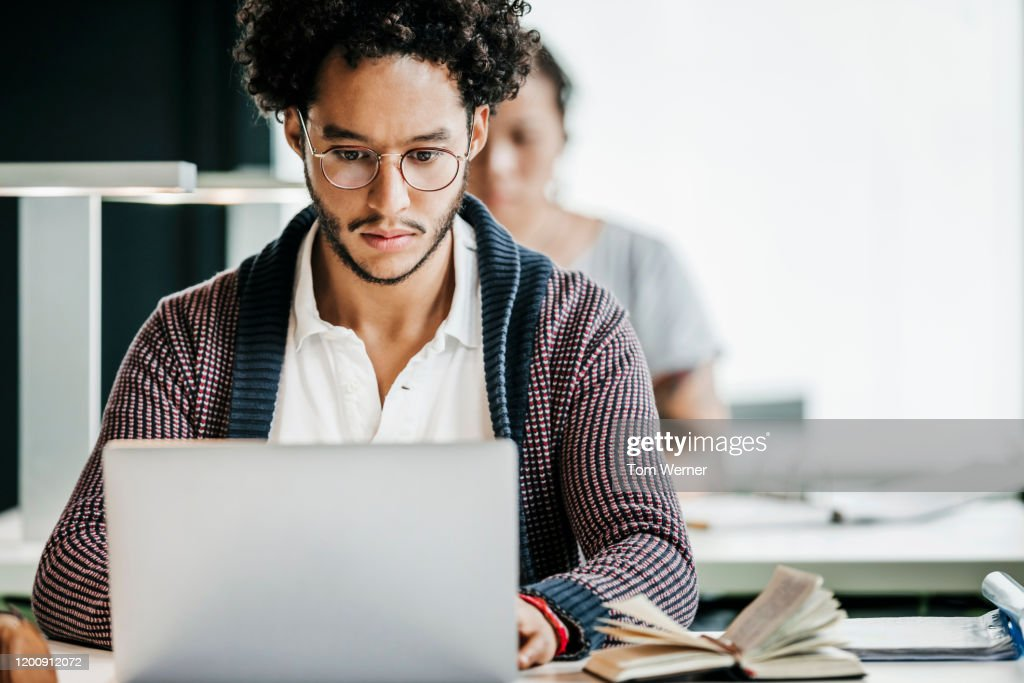 Student Concentrating On Studies In Library : Stock Photo