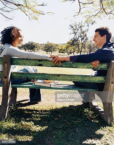 student couple on park bench - blasius erlinger stock pictures, royalty-free photos & images