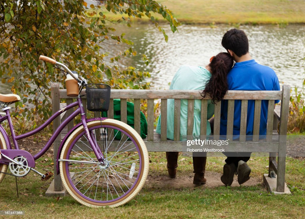 Student couple sitting on park bench : Stock Photo