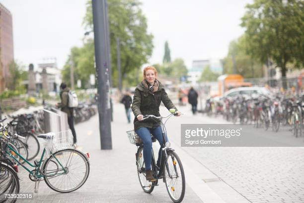 Student cycling away from library