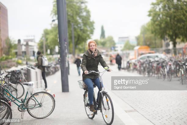 student cycling away from library - sigrid gombert stockfoto's en -beelden
