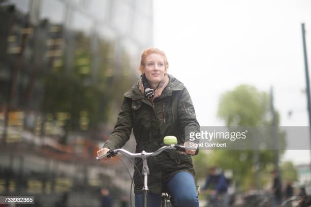 Student cycling away from University Library, Freiburg, Germany