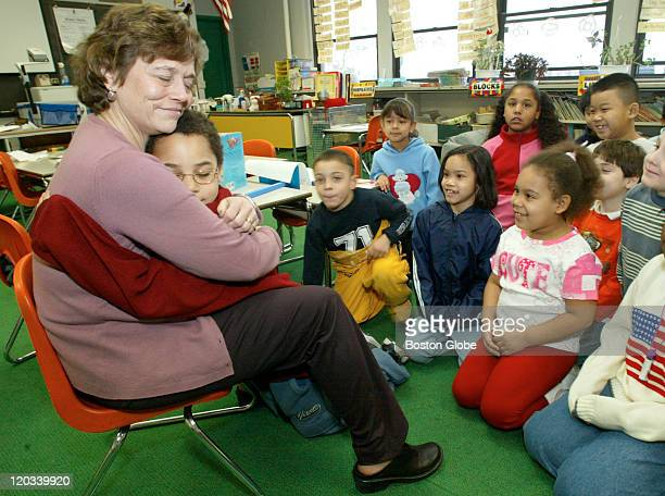 Student Dajan Gilmore gives a goodbye hug to Lori Lentini Literacy Coordinator at the Drewicz Elementary School in Lynn who stopped by Marijean...