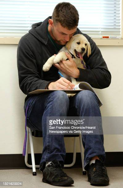 Student Daniel Fudge from Thousand Oaks fills out a log while training a puppy at Bergin University of Canine Studies in Rohnert Park, Calif., on...