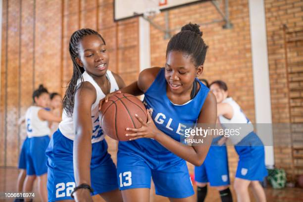 student defending basketball from opponent - face off sports play stock photos and pictures