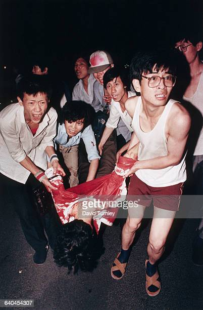 Student demonstrators carry a bloodsoaked victim away from Tiananmen Square during the PLA's violent crackdown on a peaceful demonstration