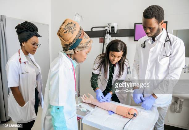 student doctors working on prosthetic arm in medical school - junior doctor stock pictures, royalty-free photos & images