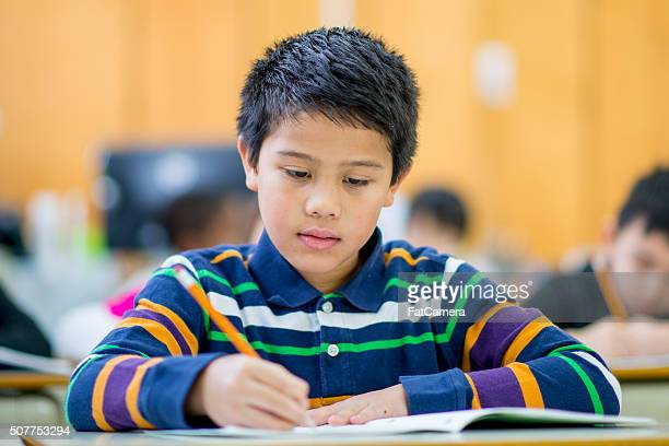 Student Doing Homework from His Notebook