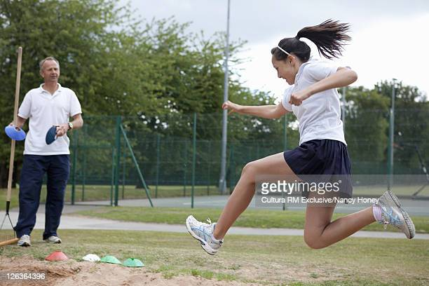 Student doing long jump outdoors