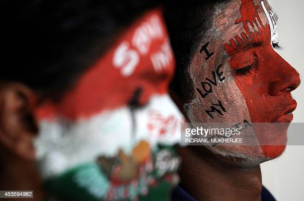 A student dozes off as waits for the paint to dry on their faces adorned with social messages and the colours of the Indian tricolour on the eve of...