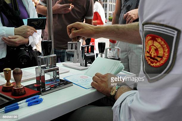 A student dressed as a former East German officer proposes to tourists to stamp their passports with GDRlike visas or with border passing stamps of...