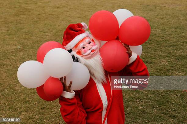 Student dressed as Santa Claus posees for the photograph at Institute Of Management Studies on the eve of Christmas on December 23, 2015 in Noida,...