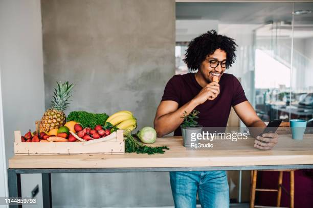 student eating carrot and using phone - snack stock pictures, royalty-free photos & images