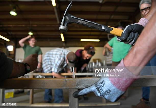 Student Eddie Haun right hammers in nails as he and other students learn how to make concrete forms during the Construction Careers Now program at...