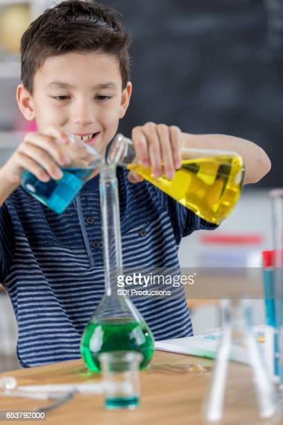 student enjoys mixing liquids in chemistry class - volume fluid capacity stock pictures, royalty-free photos & images