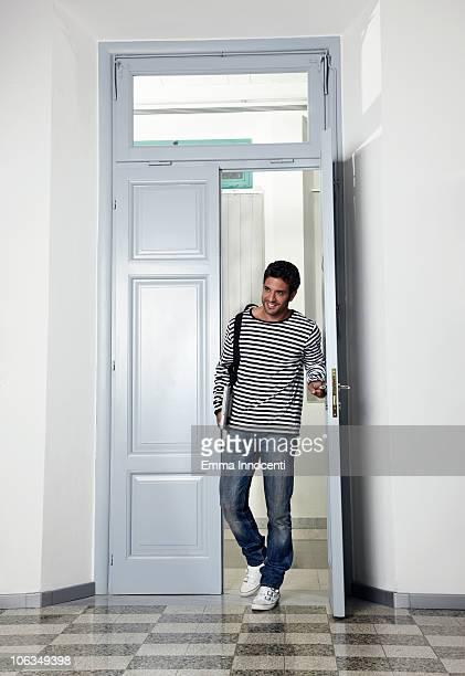 Student entering room through doorway