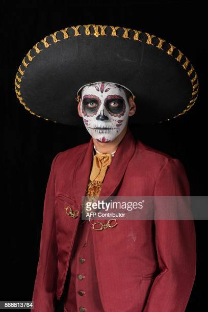 Student Ernesto Galvan poses for a photograph disguised as Catrina during a Catrina competition at the University of Michoacan in Morelia Mexico on...