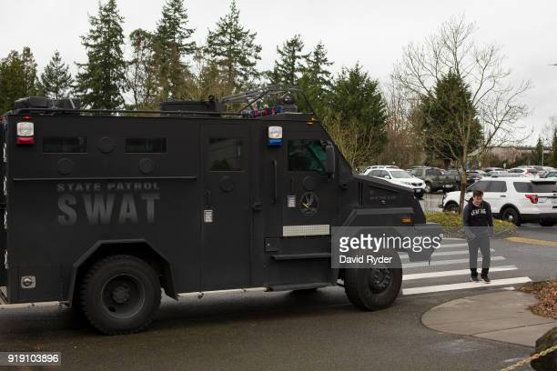 Student exits campus near a SWAT team vehicle after a threat of an active shooter shut down campus at Highline College on February 16, 2018 in Des...