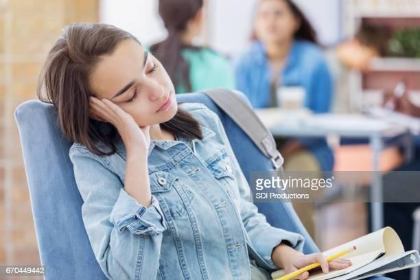 Student valt in slaap tijdens het studeren in de bibliotheek